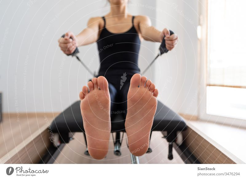 Young woman exercising on pilates reformer bed, feet close up young girl fitness exercise gym equipment training healthy body workout lifestyle flexibility