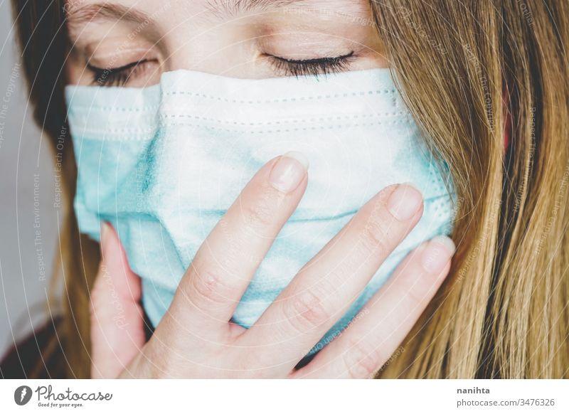 Young woman wearing a protective face mask covid 19 flu influenza coronavirus pandemic epidemic illness respiratory illness social distance contagion risk