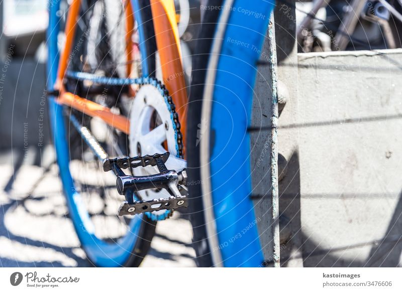 Closeup of a colorful hipster urban bicycle. bike detail chrome retro transportation vintage chain wheel blue orange metal old closeup crankset gear power