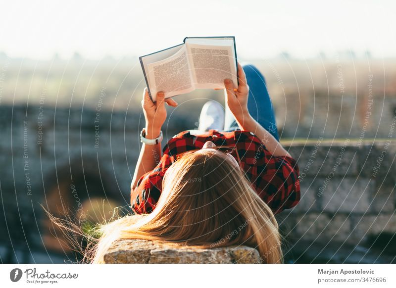 Young woman reading a book outdoors young outside joy studying student enjoying lifestyle spring summer lying leisure girl female people person adult caucasian