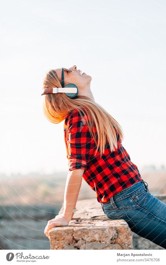 Young woman listening to the music with headphones outdoors in sunset young outside enjoying joyful wireless technology casual lifestyle cool mobile adult