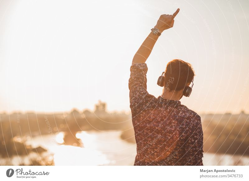 Young man listening to the music with headphones outdoors in sunset young male guy outside enjoying joyful dancing wireless technology casual lifestyle cool
