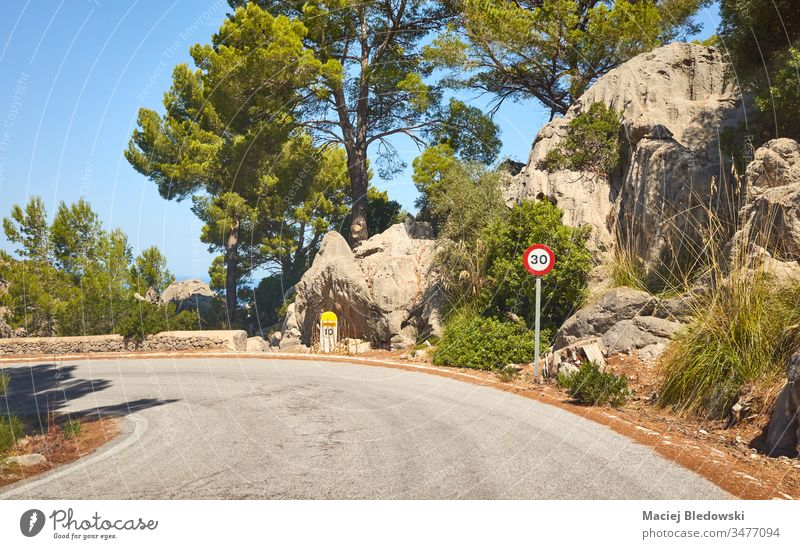 Scenic road with speed limit sign, Mallorca, Spain. drive journey trip mountain travel landscape nature traffic sign rock 30 curve tree