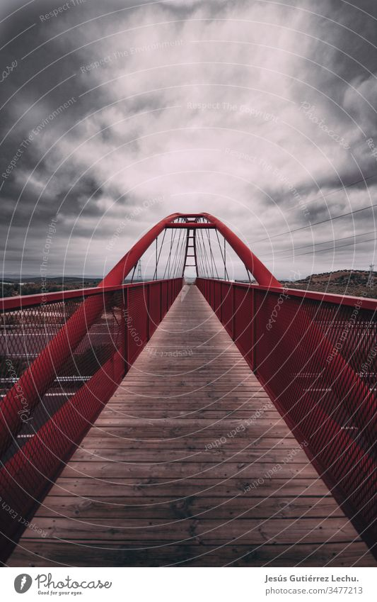 Red bridge with a long wooden path and a cloud sky red bridge Bridge railing Bridge construction pathway could sky Clouds in the sky skyline roads