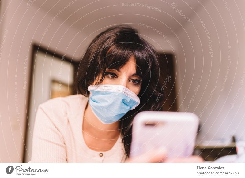 Female at home in breathing medical respiratory mask on her face using mobile phone. Chinese pandemic coronavirus, virus covid-19. Quarantine, prevent infection concept. Focus on her face.