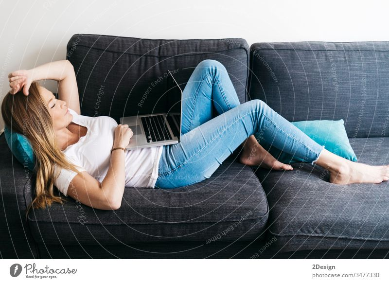 Pretty long haired female sitting on sofa with portable computer working remotely from home. woman using room relaxation smile typing communication modern
