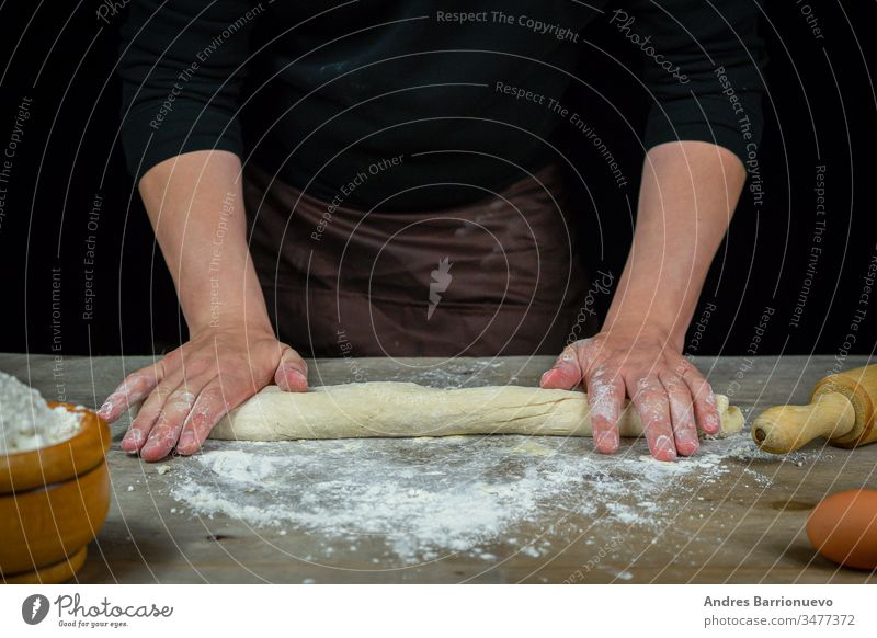 Man hands kneading bread dough on a wooden table with black background food flour wheaten meal loaf cookery organic gourmet cooking bakery healthy male cuisine