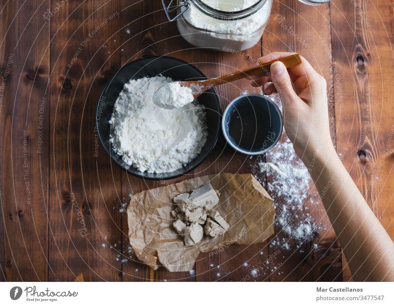 A woman's hand adding flour to make sourdough. Bakery concept. Sourdough Dough knead spoon yeast processing glass jar homemade wooden bottom dark background