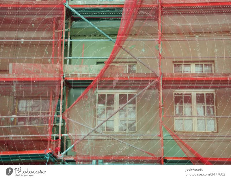 Renovation of the green facade with reddish scaffolding Construction site Facade Scaffold Covers (Construction) Build Authentic Moody Protection Change
