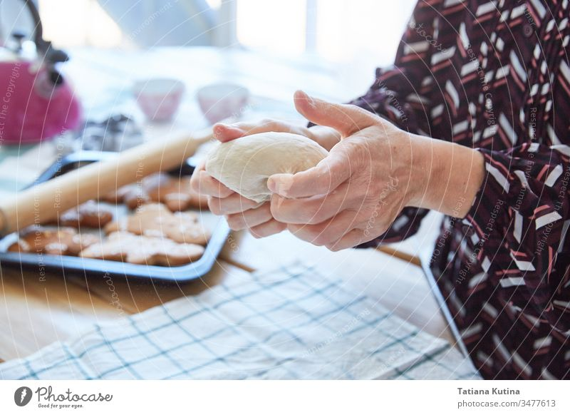 Female hands of an elderly woman knead the dough. Grandma makes cookies. Light background. female senior flour old table home kitchen baker aged preparation
