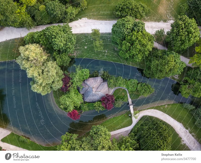 Aerial view over a park, canal with coloRed trees. above aerial travel top landscape green forest drone water vertical tourism wonderful Munich summer river