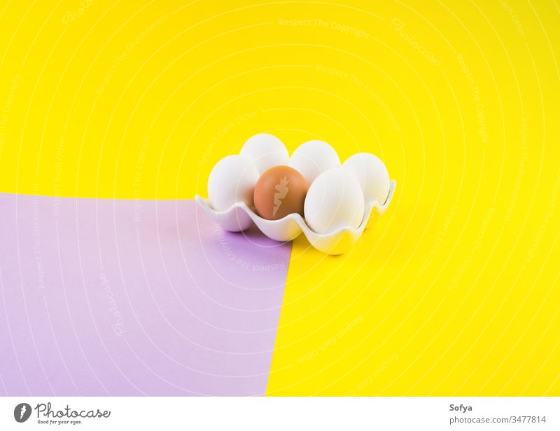 White and one brown egg on yellow and purple easter eggs color duotone bold unique different food holiday celebrate background design layout frame creative