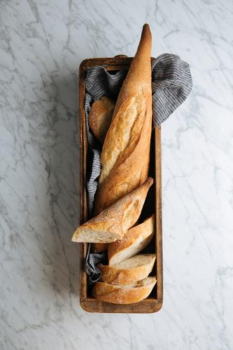 Fresh cut bread on wooden tray baguette fresh slice table bakery loaf crust homemade artisan marble food tasty delicious meal rustic pastry baked bun healthy