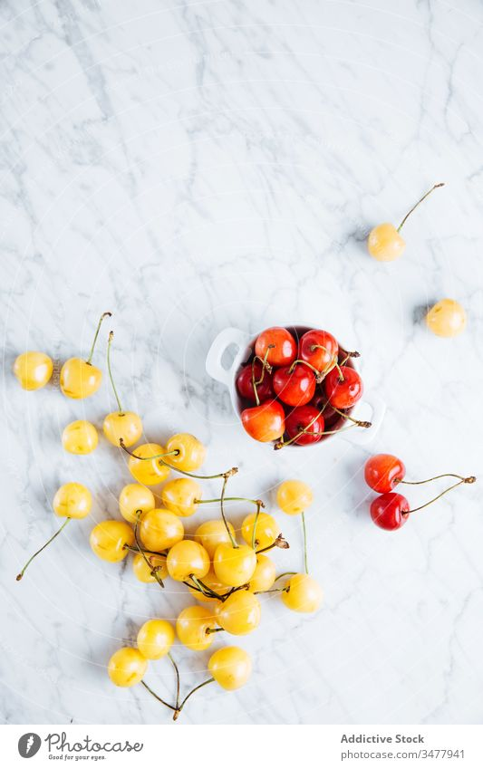 Fresh cherry on marble table red yellow berry fruit fresh ripe natural food healthy bowl glass pot pile plant stalk vitamin sweet tasty delicious raw season