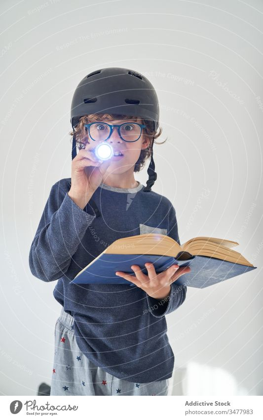 blond kid in pajamas with a helmet a flashlight and a book playing research children game protect happiness enjoyment room indoor party comfort emotional