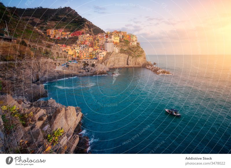 Wonderful scenery with small colorful town on rocky coast washing by calm ocean water during sunset sea boat idyllic cliff sky shore coastline paradise tourism