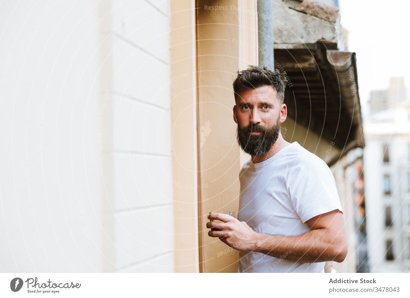 Bearded guy with hot drink resting on balcony man morning casual stand modern home apartment male beard adult handsome lifestyle relax early fresh beverage