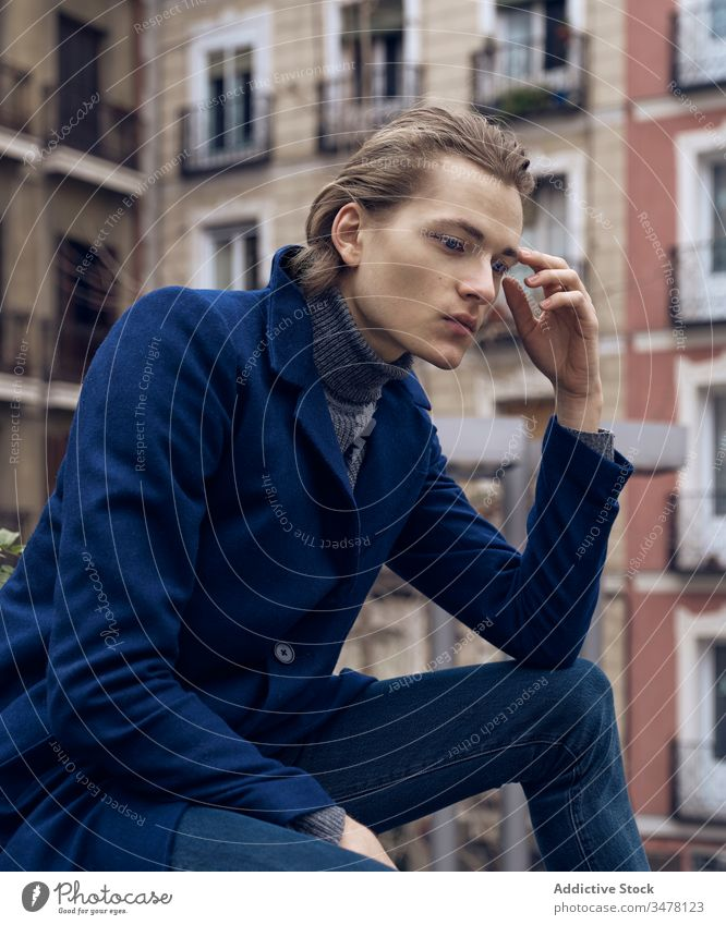 Pensive man in stylish wear sitting on street pensive thoughtful style trendy serious think urban city young male elegant modern ponder coat contemplate