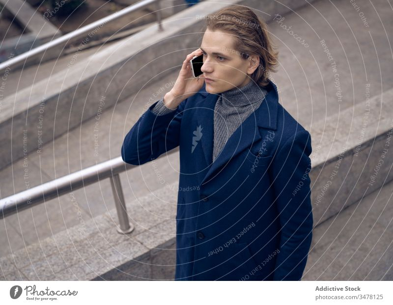 Trendy man using cellphone in city smartphone style trendy serious urban stone street gadget device mobile connection internet elegant check communicate male