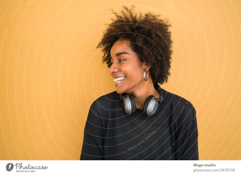 Portrait of young afro american woman. beautiful yellow background adult hairstyle lovely wall standing image look gesture cheerful lifestyle ethnicity mixed