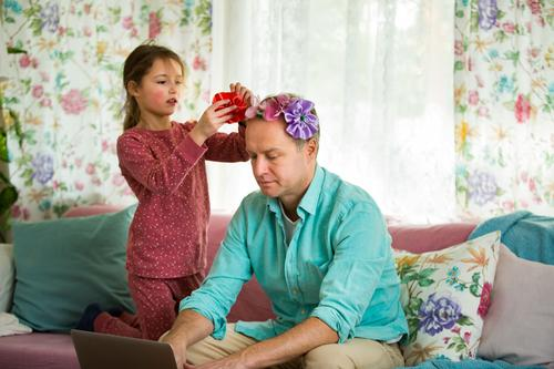 Child playing and disturbing father working remotely from home. Little girl combing daddy's hair and making hairstyle. Man sitting on couch with laptop. Family spending time together indoors.