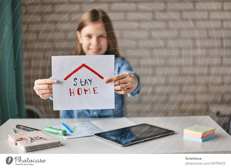 A beautiful teenage girl holds a sign saying stay at home. The girl recommends staying at home during the quarantine. Self-isolation, social distance childhood