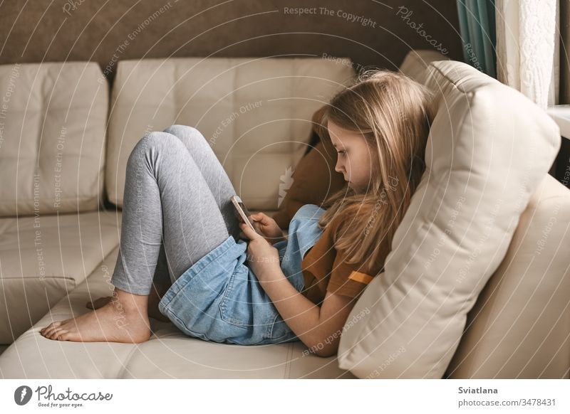 A pretty girl communicates with her friends via messenger during the quarantine. Self-isolation, communication, social distance during quarantine sofa