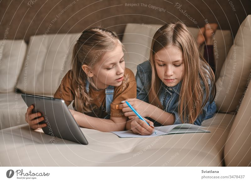 Two beautiful sisters do their homework during quarantine. Children use gadgets for learning. Education, distance learning, home schooling during quarantine