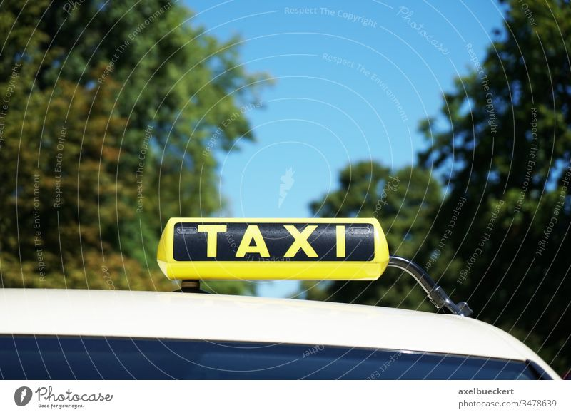 german taxi sign on car roof cab yellow taxi stand taxicab closeup close-up traffic transport transportation travel nature tree sky copy space copyspace symbol