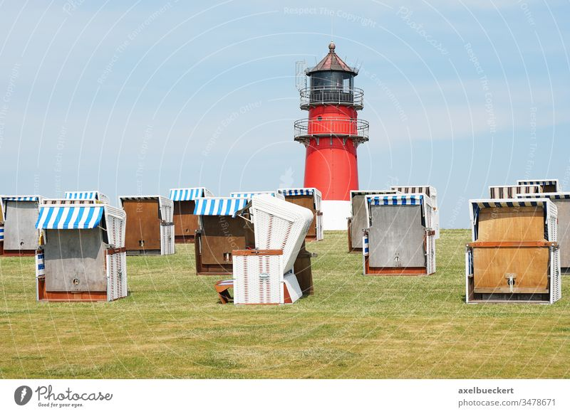dike with hooded beach chairs and lighthouse büsum strandkorb dyke green busum north sea coast germany canopied roofed landscape travel vacation holiday coastal