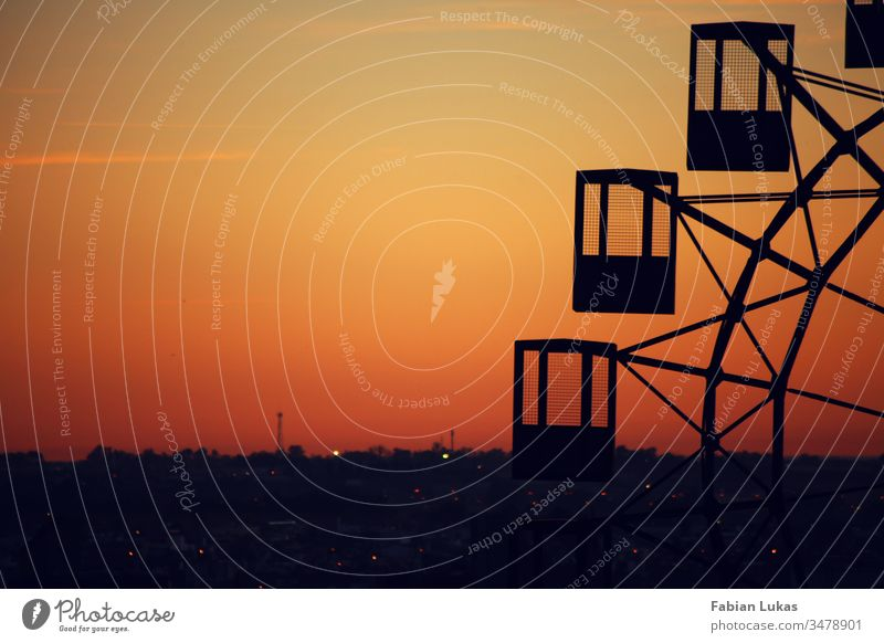 Old Ferris wheel at sunset over a city Shadow Silhouette Sunset Orange Yellow Sky Exterior shot Deserted Evening