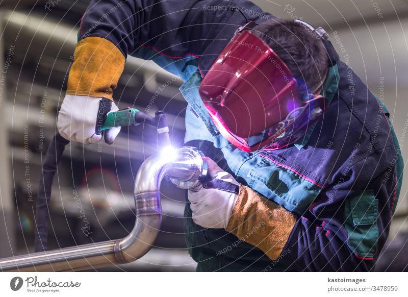 Industrial worker welding in metal factory. welder industry inox steel tube craftsman industrial manufacturing engineering stainless steel skill mask safety