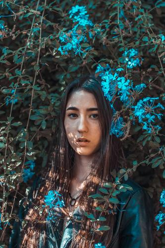Young girl surrounded by blue flowers Front view Upper body Portrait photograph Multicoloured Interior shot Blur Colour photo head Lady attractive long hair
