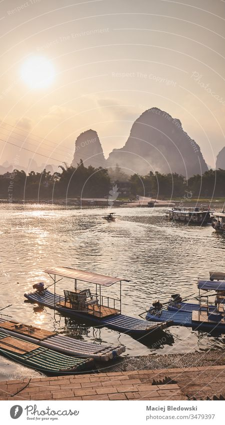 Bamboo rafts at Li River bank in Xingping at sunset, China. bamboo boat travel Asia beautiful dusk filtered hill karst landscape li mountain nature picture pier