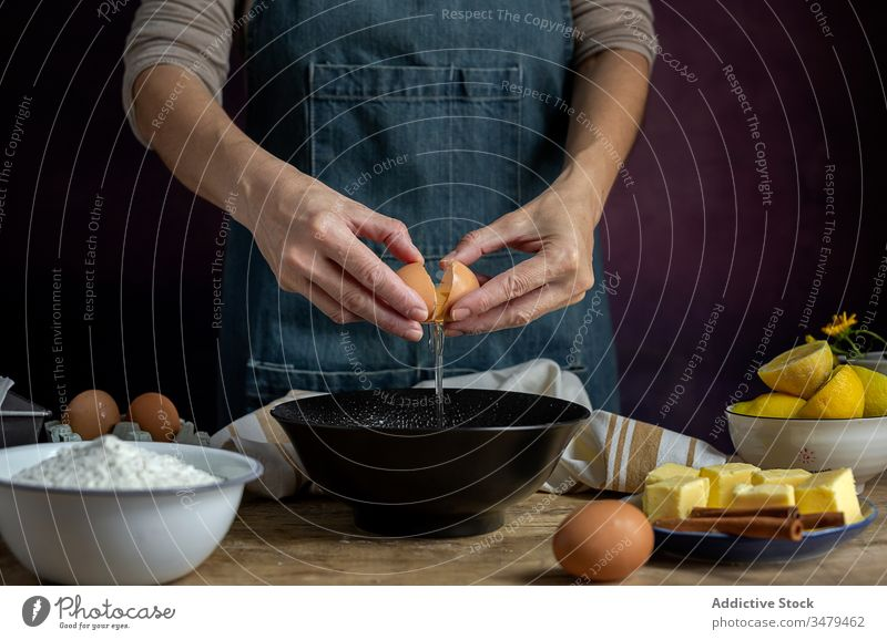 Crop woman breaking egg into bowl cook pastry fresh female fragile eggshell ingredient food cuisine recipe organic gourmet homemade wooden table raw add dough