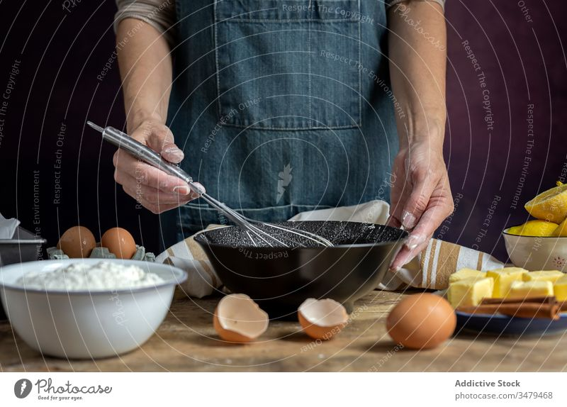 Faceless woman preparing eggs with whisk in kitchen cook ingredient bowl wooden table process food prepare cuisine fresh recipe delicious nutrition culinary