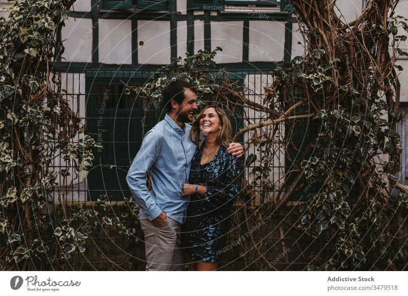 Happy couple in love hugging on street embrace city romantic together happy affection date kiss france bayonne urban bonding fence lifestyle cheerful tender