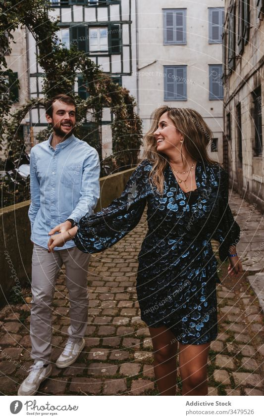 Happy couple walking on city street happy together cheerful smile casual romantic love relationship lifestyle urban girlfriend boyfriend affection old france