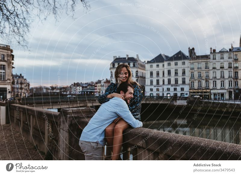 Happy couple enjoying time together in romantic city love relationship embrace happy fence stone travel boyfriend france bayonne girlfriend hug date affection