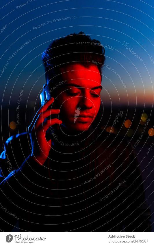 Handsome guy talking on phone on night street man neon smartphone dark red blue modern serious device illuminate gadget communication confident conversation