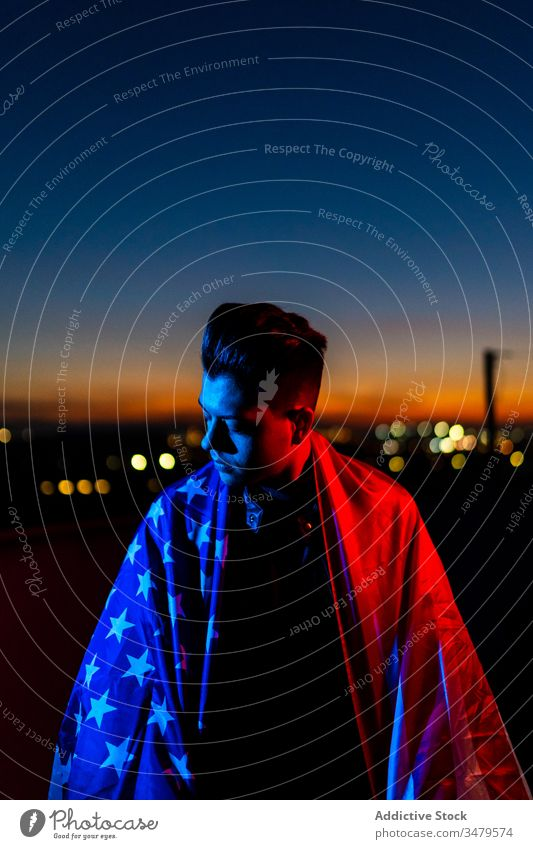 Man with American flag against night sky man american red blue patriot sunset confident freedom dark street evening nation male twilight young dusk casual