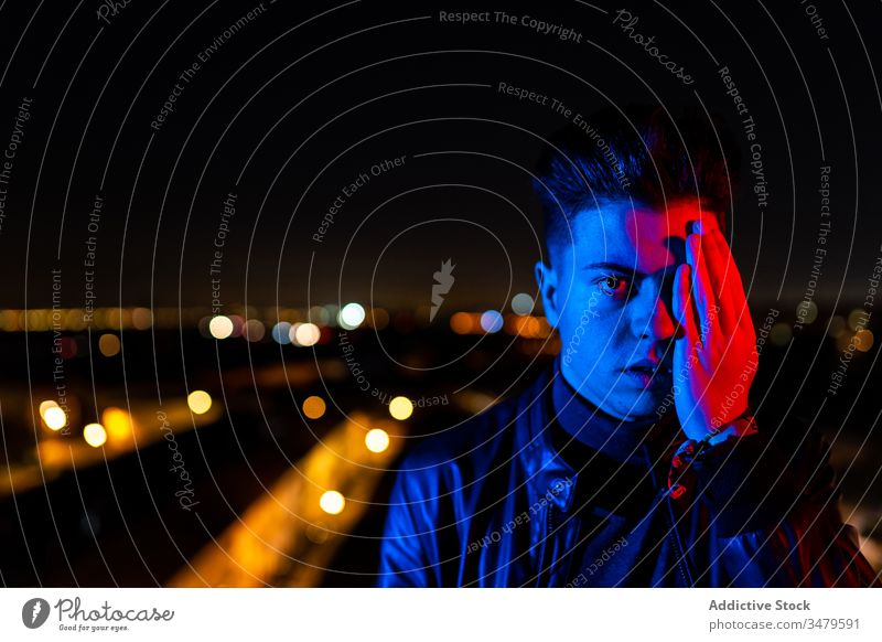 Modern man covering face under colorful illumination cover face half night illuminate concept street city urban dark male gesture young modern casual town