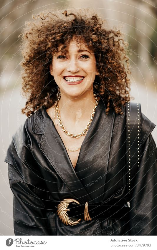Delighted retro businesswoman on street city smile leather jacket adult curly hair commute work outfit style happy female delight optimist model fashion trendy