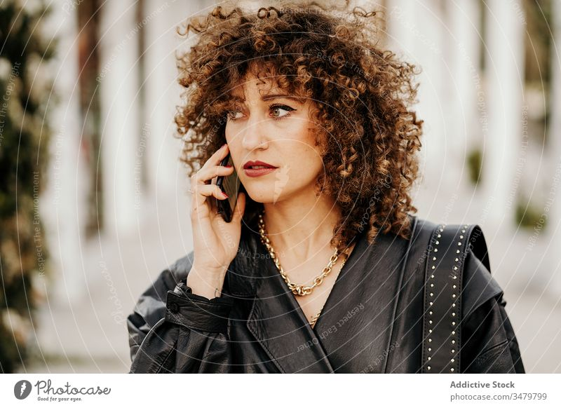 Retro businesswoman talking on smartphone in park walk speak retro path commute outfit style female old fashioned 80s cool leather jacket lifestyle road street
