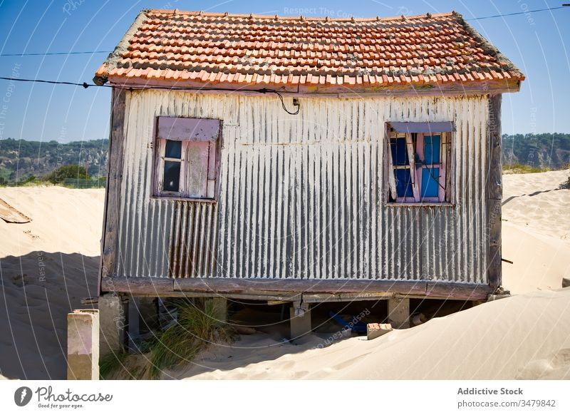 Old shabby house on sandy beach small coast building facade rural countryside exterior architecture sunny blue sky construction structure residential window