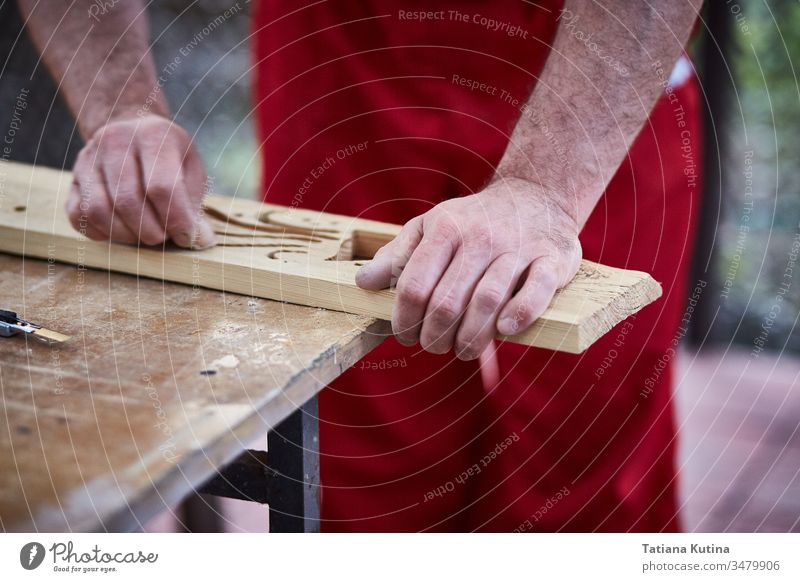 Closeup of male hands carpenter using sandpaper to sand wooden detail. carpentry closeup craft craftsman diy industry job sanding tool worker workshop business