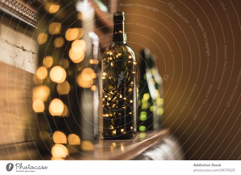 Decorative bottles with garlands inside decor light design interior decoration style wooden composition illuminate glass wall row arrangement festive bright