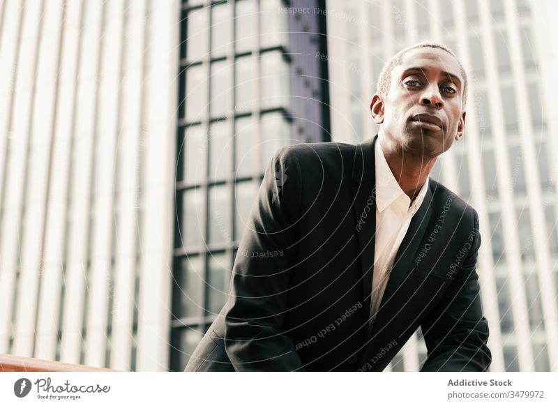 Confident black businessman leaning on railing confident modern street urban ethnic city suit male hand in pocket professional elegant entrepreneur success