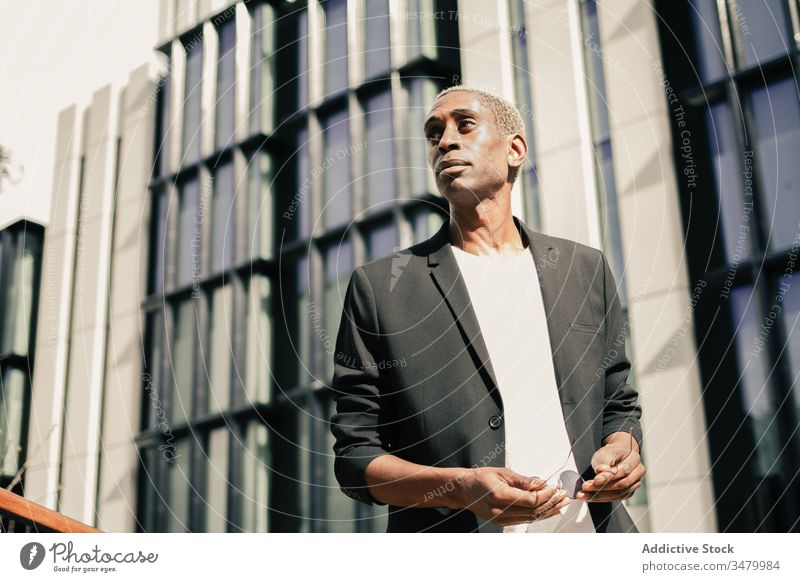 Stylish black businessman on street style city building success ethnic urban modern confident male professional entrepreneur contemporary executive smart