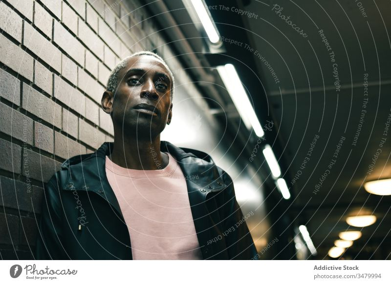 African American man leaning on wall style urban illuminate corridor ethnic modern confident male casual trendy fashion cool building city contemporary black